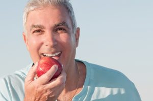 older man biting into apple