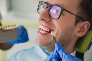 man in dental chair missing tooth preparing for dental crown
