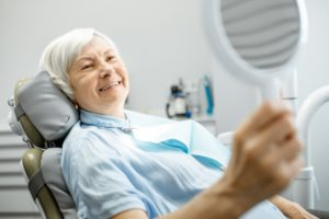 older woman admiring her smile with implant-retained dentures in the mirror
