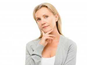 woman thinking over the dental implant cost